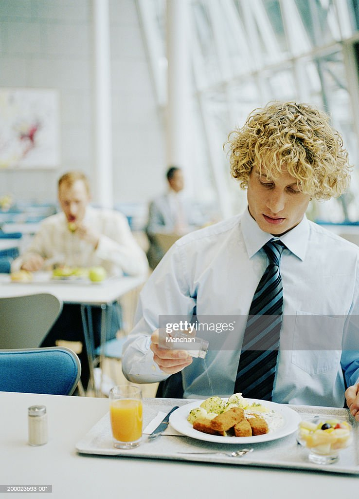 Young businessman in canteen pouring salt on to food