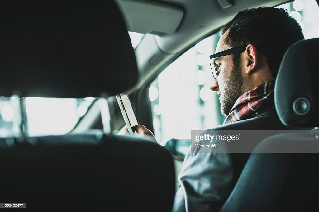 Young businessman in car looking on cell phone