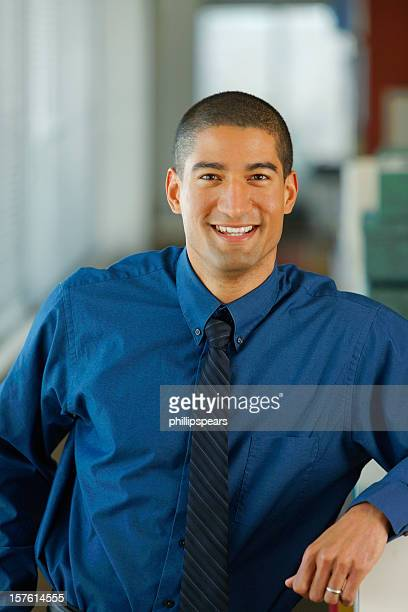 Young businessman in dark blue shirt smiling in his office