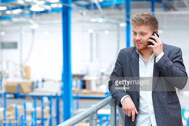 Jeune homme d'affaires à l'aide de téléphone mobile en usine