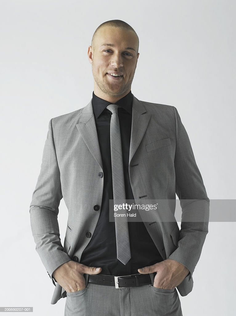 Young businessman in grey suit, smiling, portrait