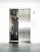 Young businessman in lift, portrait, view through open door