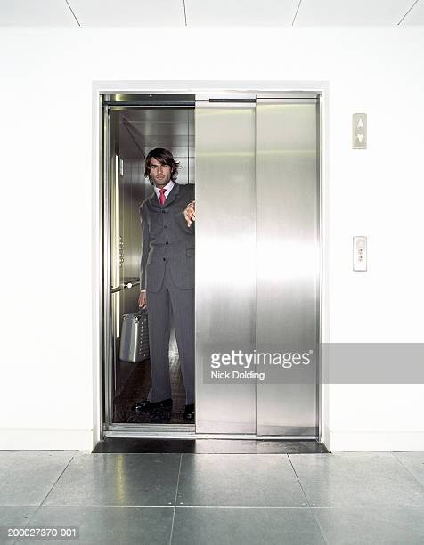 Young businessman in lift, portrait, view through open door