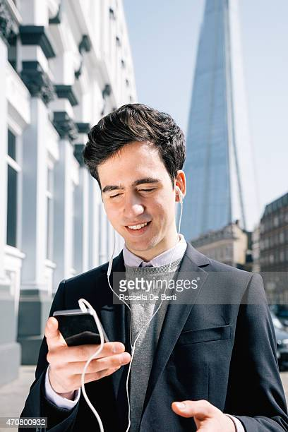Young businessman in London making a video call with earbuds