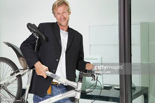 Young businessman in office building with bicycle.