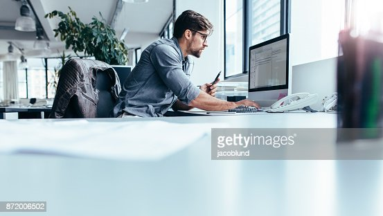 Young businessman in office working on computer : Stock Photo