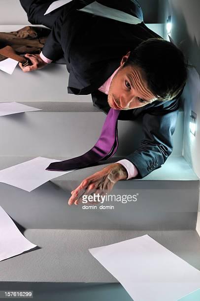 若いビジネスマンのスーツは、フォーリングダウンの階段