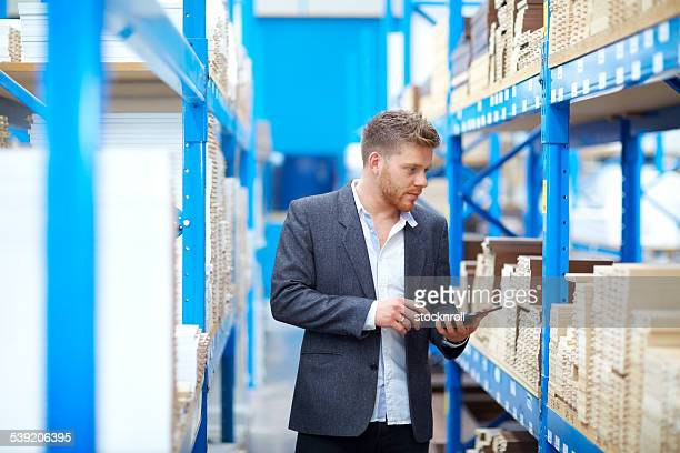 Young businessman in warehouse checking inventory