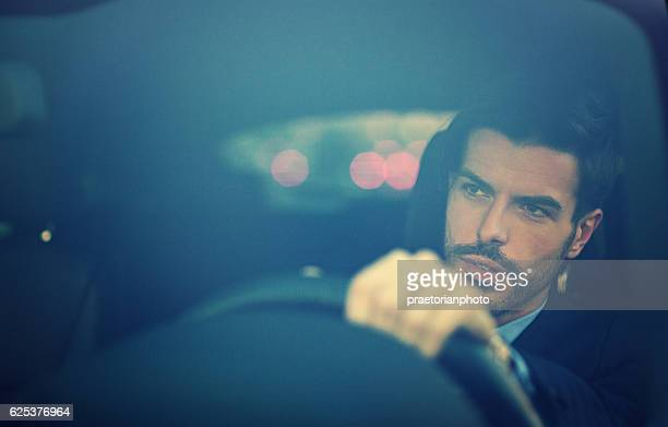 Young businessman is driving in the city