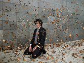 Young businessman kneeling on pavement amongst blowing leaves