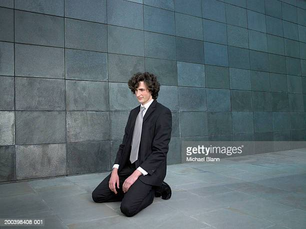 Young businessman kneeling on pavement
