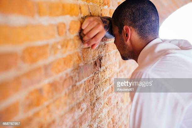 Young businessman leaning against brick wall