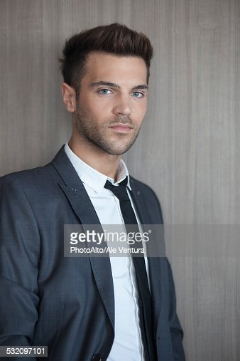 Young businessman leaning against wall, portrait