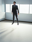 Young businessman levitating in office