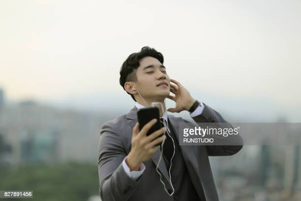 Young businessman listening music through mobile phone outdoors