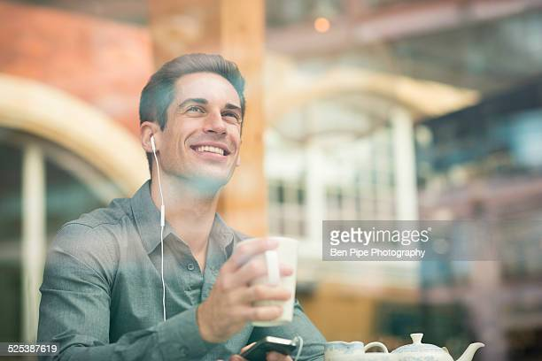 Young businessman listening to earphones in cafe window seat, London, UK