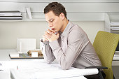 Young businessman looking at blue prints on desk