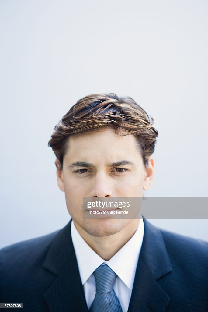 Young businessman looking at camera, portrait, head and shoulders : Stock Photo