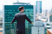 Portrait of young businessman standing on balcony and looking at city view