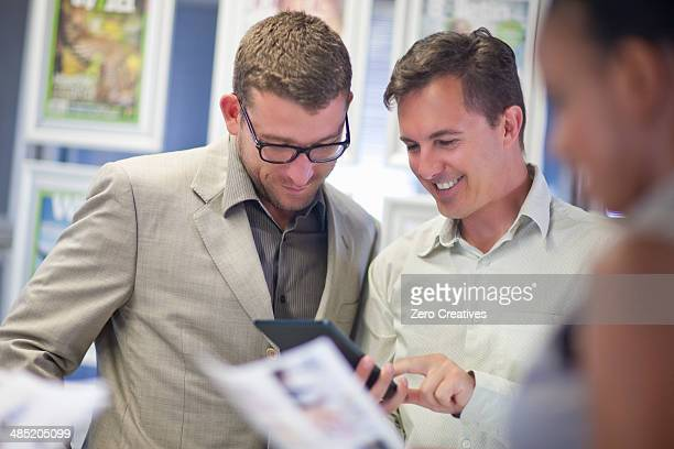Young businessman looking at colleagues digital tablet