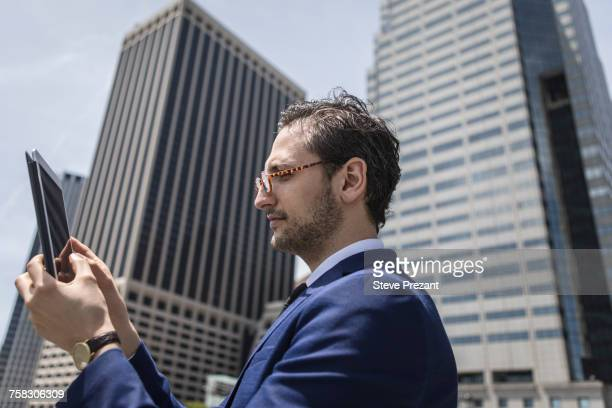 Young businessman looking at digital tablet by New York skyscrapers, USA