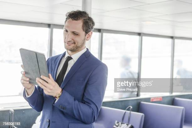 Young businessman looking at digital tablet on passenger ferry