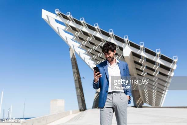 Young businessman looking at smartphone outdoors