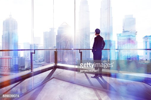 Young businessman looking out the city in the office . morning scene. . : Stock Photo