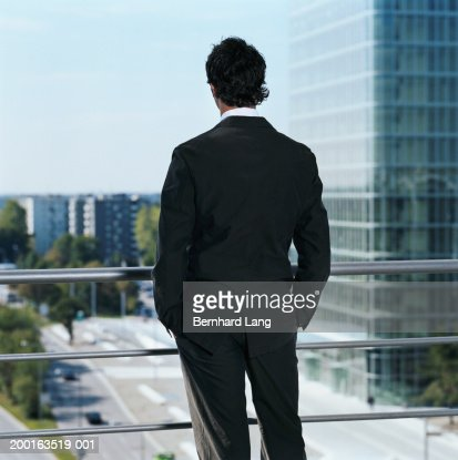 Young businessman looking out window, hands in pocket, rear view : Stock Photo