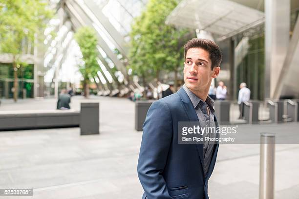 Young businessman looking over his shoulder at Broadgate Tower, London, UK