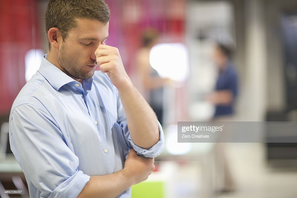 Young businessman looking stressed in office