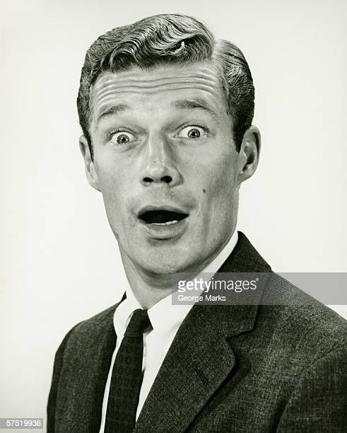 Young businessman looking surprised, posing in studio, (B&W), portrait