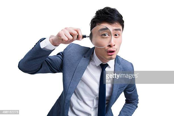 Young businessman looking through magnifying glass