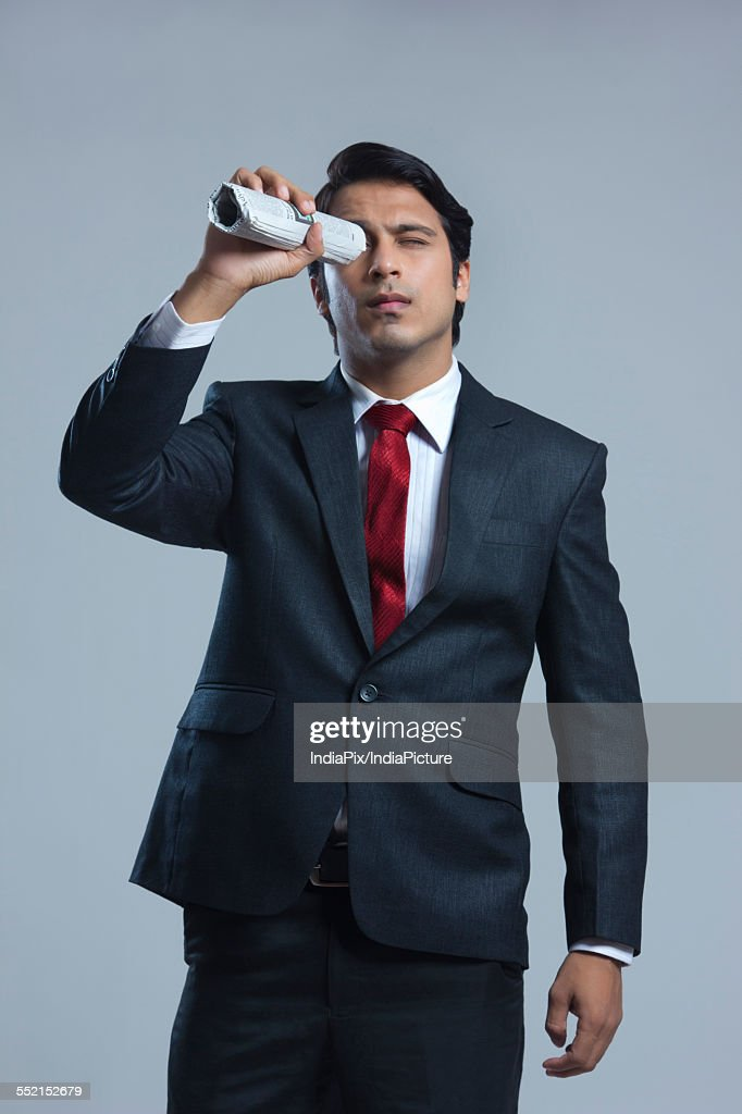 Young businessman looking through newspaper over gray background : Stock Photo