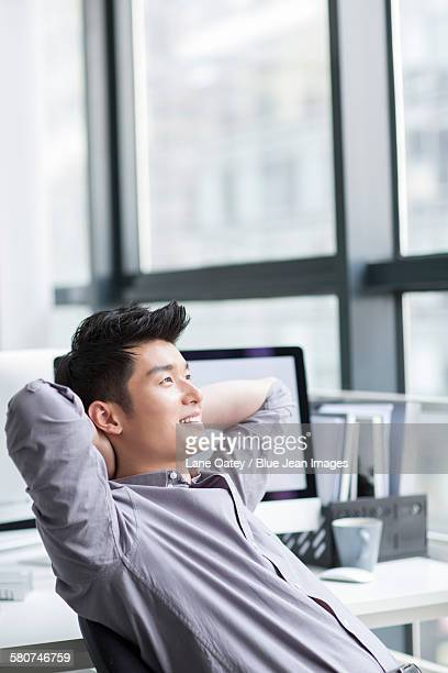 Young businessman looking through window in office