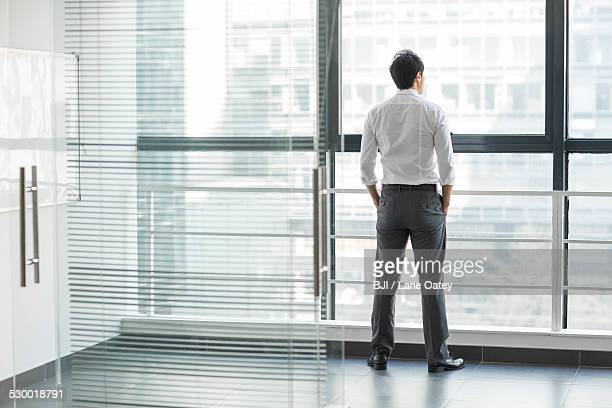 Young businessman looking through window