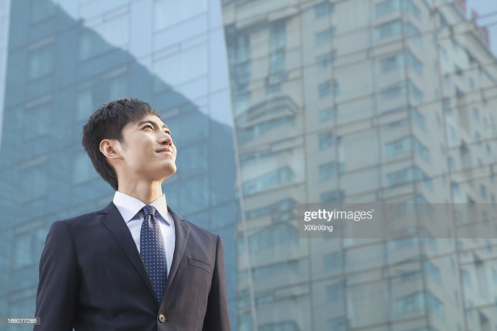 Young Businessman Looking Up, Glass Building,  Portrait : Stock Photo