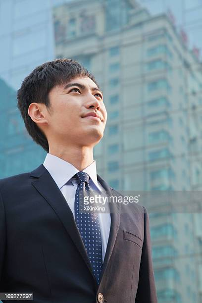 Young Businessman Looking Up, Glass Building, Portrait