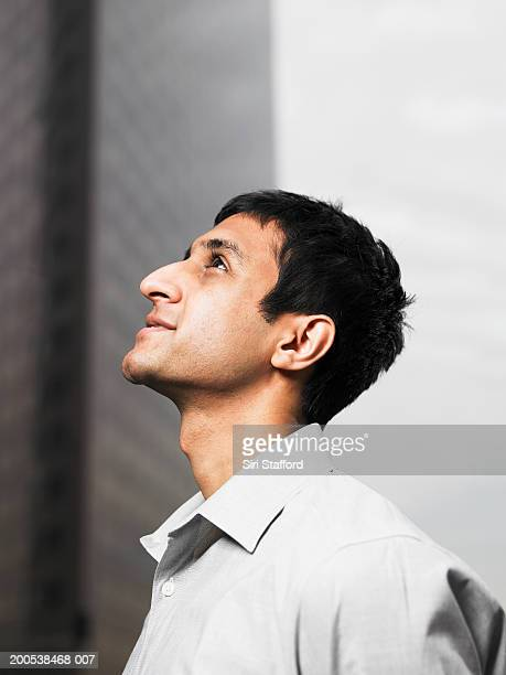 Young businessman looking up, profile
