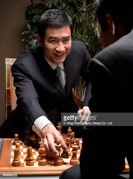 Young businessman making move in chess game.
