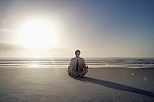 Young Businessman Meditating on the Beach