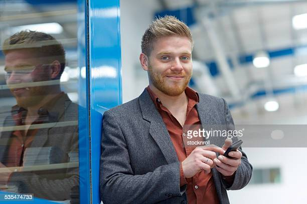 Young businessman on factory shopfloor with mobile phone