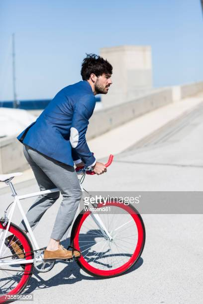 Young businessman on fixie bike outdoors