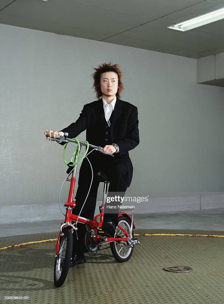 Young businessman on folding bicycle, portrait