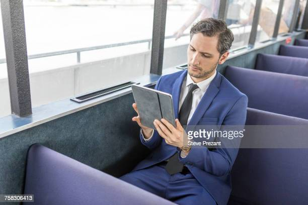 Young businessman on passenger ferry looking at digital tablet