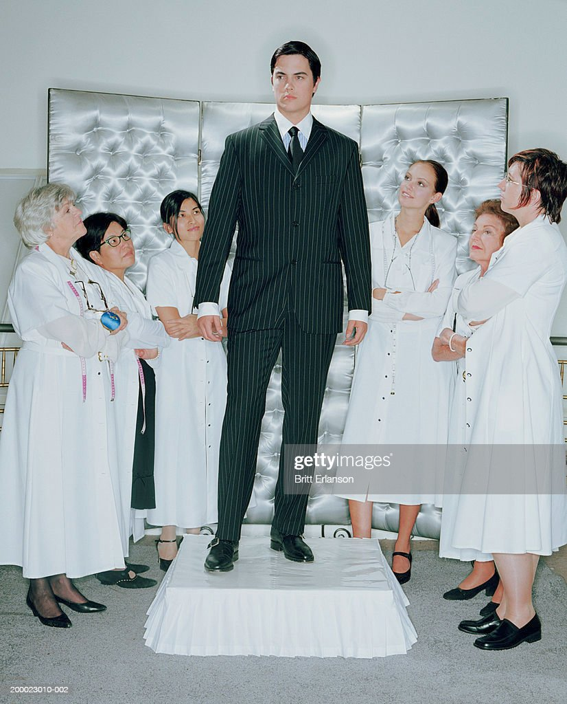 Young businessman on plinth, surrounded by group of women