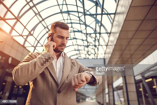 Young businessman on the phone checking the time.