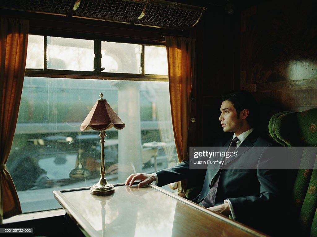 Young businessman on train staring out of window : Stock Photo