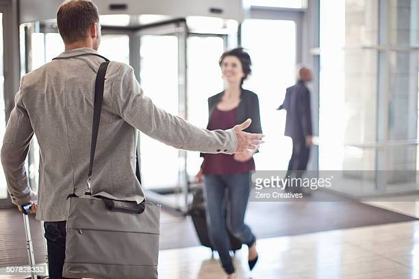 Young businessman opening arms for girlfriend in conference centre atrium
