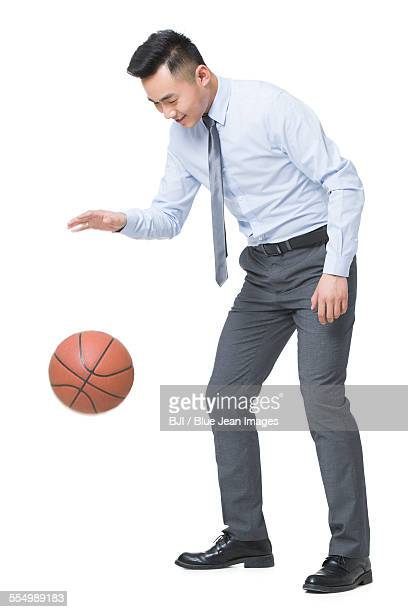 Young businessman playing basketball